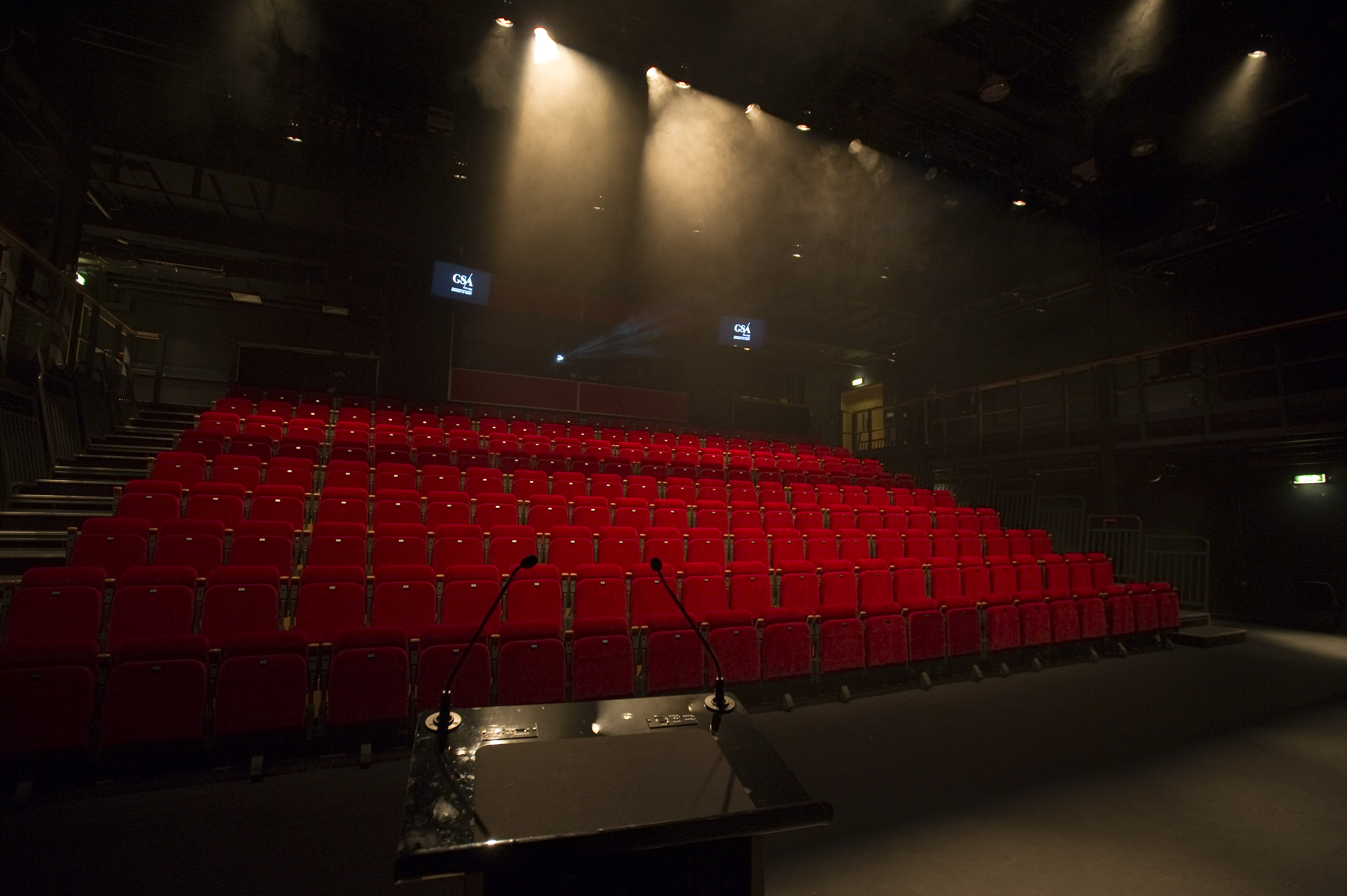 Theatre hall with red velvet seats and staging lights.
